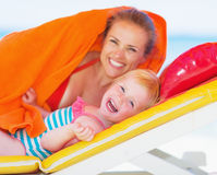Portrait of happy mother and baby laying on chaise-longue Stock Image