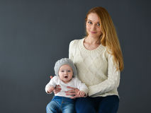 Portrait of happy mother and baby, sitting on gray background Stock Photo