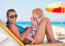 Portrait of happy mother and baby on sun bed Stock Photos