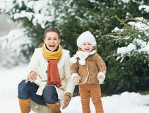 Portrait of happy mother and baby in winter park Royalty Free Stock Images
