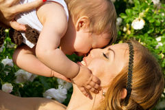 Portrait of happy mother and child on a background of flowers Royalty Free Stock Photo