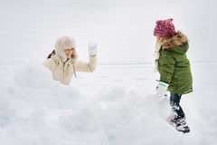 Portrait of happy mother and child playing snowball fight Royalty Free Stock Images