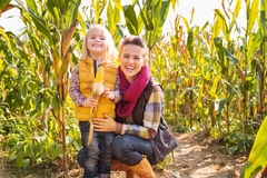 Portrait of happy mother and child staying in corn field on farm Stock Image