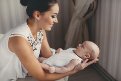 Portrait of happy mother and child. A young mother,brunette,hair pulled back,white sleeveless blouse, spending time together with their newborn son at home in Royalty Free Stock Photos