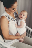 Portrait of happy mother and child. A young mother,brunette,hair pulled back,white sleeveless blouse, spending time together with their newborn son at home in Stock Photography