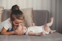 Portrait of happy mother and child. A young mother,brunette,hair pulled back,white sleeveless blouse, spending time together with their newborn son at home in Stock Images