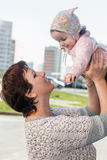 Portrait of a happy mother. Portrait of a happy mother at city with the child on hands Stock Photo