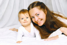 Portrait happy mother and cute baby on the bed home Stock Photo