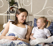 Portrait of happy mother and daughter in bed hugging and smiling Stock Photo