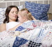 Portrait of happy mother and daughter in bed hugging and smiling Stock Images