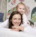 Portrait of happy mother and daughter in bed hugging and smiling Royalty Free Stock Photos