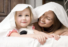 Portrait of happy mother and daughter in bed hugging and smiling Stock Photography