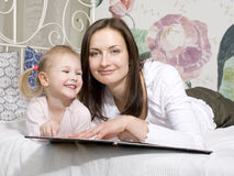 Portrait of happy mother and daughter in bed hugging and smiling Royalty Free Stock Image