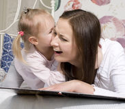 Portrait of happy mother and daughter in bed hugging and smiling Royalty Free Stock Photography