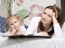 Portrait of happy mother and daughter in bed hugging and smiling Royalty Free Stock Images
