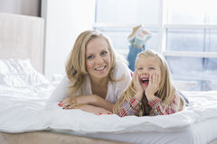 Portrait of happy mother and daughter lying in bed Royalty Free Stock Photos