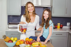 Portrait of happy mother and daughter preparing fruit juice Royalty Free Stock Photo
