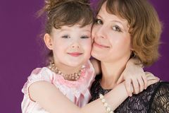 Portrait of a happy mother and daughter in a purple room. The daughter hugging mother stock image