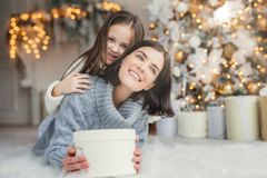 Portrait of happy mother and daughter spend free time together, embrace each other, have pleasant smiles, hold wrapped present box stock photography