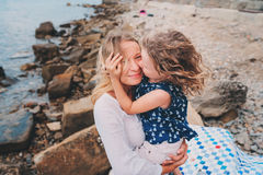 Portrait of happy mother and daughter spending time together on the beach on summer vacation. Happy family traveling, cozy mood. Child kissing mother Royalty Free Stock Photo