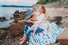 Portrait of happy mother and daughter spending time together on the beach on summer vacation. Happy family traveling, cozy mood. Stock Photos