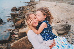 Portrait of happy mother and daughter spending time together on the beach on summer vacation. Happy family traveling, cozy mood. Child kissing mother Stock Photo