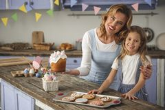 Glad family demonstrating ready bakery. Portrait of happy mother and daughter standing in the cuisine and showing homemade easter pastry. Copy space in left side Stock Images