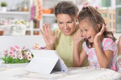 Portrait of happy mother and daughter using modern tablet stock photos