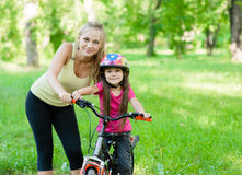 Portrait of a happy mother embracing daughter who learns to ride Royalty Free Stock Photography