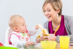 Happy mother giving a fresh and nutritious banana to her cute baby girl royalty free stock photo