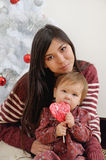 Portrait of happy mother and her baby near Christmas tree Royalty Free Stock Images