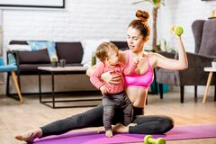 Mother exercising with her baby son at home. Portrait of a happy mother with her baby son exercising with dumbbells at home stock photography