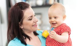 Portrait of happy mother with her cute baby girl. At home stock photos