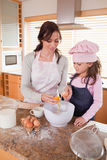 Portrait of a happy mother and her daughter baking Stock Image