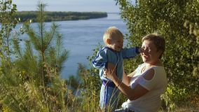 Portrait of happy mother and her little son sitting against river background on a sunny summer day stock video footage