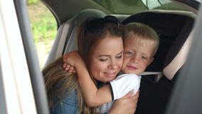 Portrait of a happy mother with her son in the car, the boy in the car seat. Portrait of a happy loving mother with her son in the car, the boy is wearing a stock video