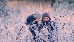 Portrait of a happy mother with her son playing in the frozen bushes.