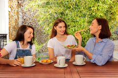 Mother having lunch with two daughters outdoors royalty free stock photo