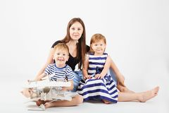 Portrait of a happy mother and her two little children - boy and. Girl. Happy family against a white background. Little kids kissing mother. Children with toys Royalty Free Stock Photography