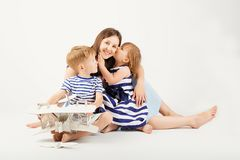 Portrait of a happy mother and her two little children - boy and. Girl. Happy family against a white background. Little kids kissing mother. Children with toys Royalty Free Stock Photos