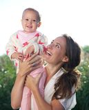 Portrait of a happy mother holding cute baby outdoors Stock Photography