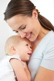 Portrait of a happy mother hugging cute baby. Close up portrait of a happy mother hugging cute baby against white background Royalty Free Stock Photos