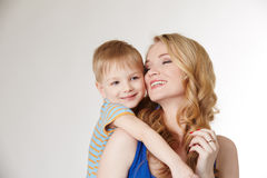 Portrait of happy mother hugging her son. In studio Royalty Free Stock Photography