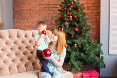 Portrait of happy mother and laughing baby holding bauble against domestic festive interior with Christmas tree. Stock Photo