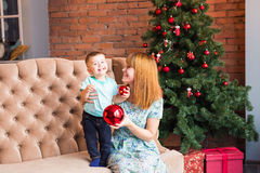 Portrait of happy mother and laughing baby holding bauble against domestic festive interior with Christmas tree. Stock Images