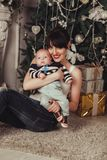 Portrait of happy mother and litle baby near decorated christmas tree with gifts. Portrait of happy mother and litle baby near decorated christmas tree with Stock Photo