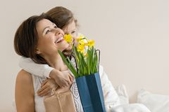 Portrait of happy mother and little daughter smiling and embracing, girl congratulates her mother with bouquet of flowers. Mom and royalty free stock photo
