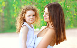 Portrait of happy mother and little daughter together in summer Stock Image