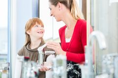 Happy mother looking with her daughter at two faucets in a sanitary ware shop royalty free stock images