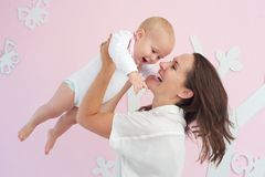 Portrait of a happy mother playing with cute baby Stock Photo